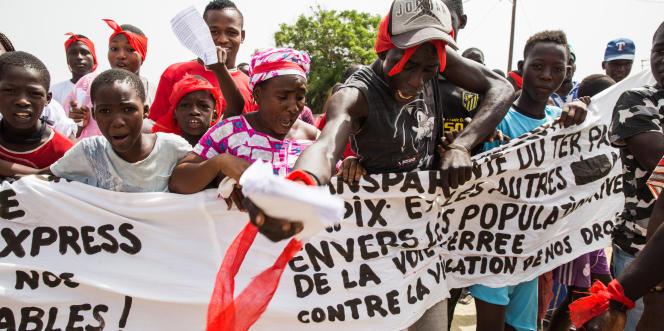 Dans la banlieue de Dakar, des manifestants anti-TER arborent la couleur rouge et porte une bannière lors de leur marche de protestation, le 30 septembre 2017. Ils réclament une meilleure indemnisation pour l'expropriation de leurs maisons.