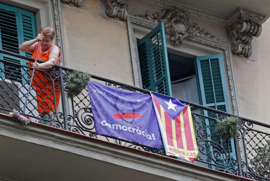 Une femme nettoie un balcon trois jours après la tenue du référendum d'autodétermination, le 4 octobre, à Barcelone.