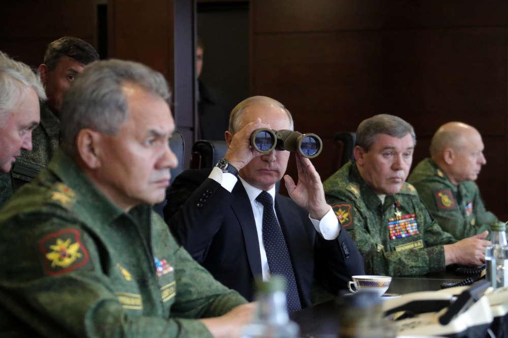 Le président russe, Vladimir Poutine, au centre, le ministre de la défense, Sergueï Choïgou, à gauche, et le chef de l'état-major général des forces armées russes, Valéri Guérassimov, à droite, regardent le déroulement des exercices à Luzhsky, près de Saint-Pétersbourg, en Russie, le 18 septembre.