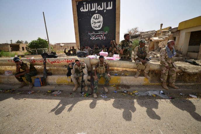 Les forces irakiennes devant un drapeau de l'Etat islamique dans Hawija, après la libération de la ville, jeudi5 octobre.