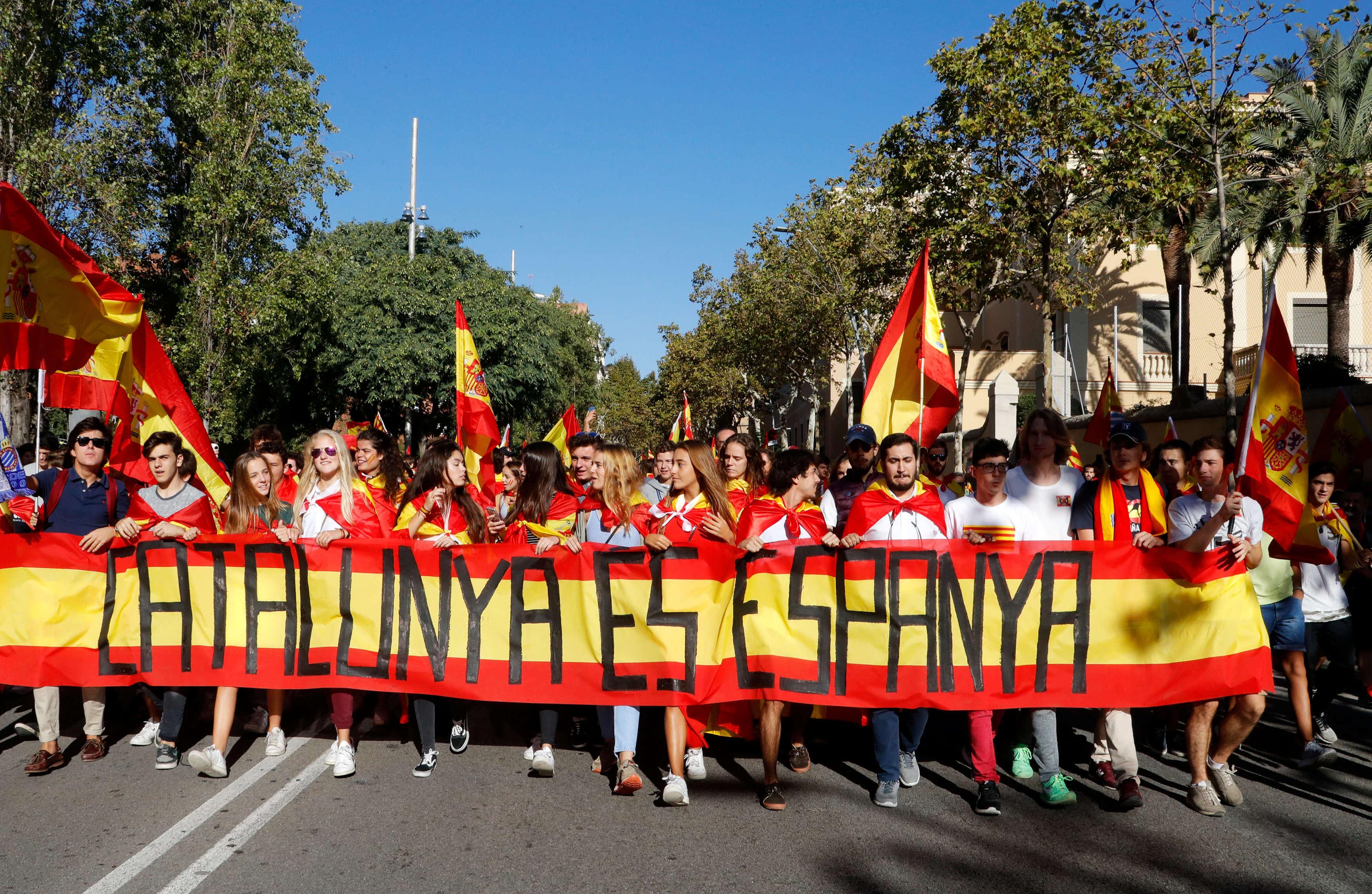 Des manifestants derrière une bannière qui indique, en catalan, les mots suivants : « La Catalogne, c'est l'Espagne».