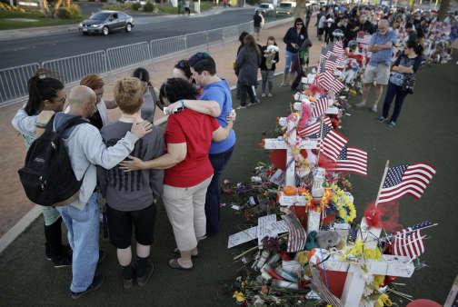 Nombreux sont ceux qui sont venus se recueillir sur le mémorial improvisé à la suite de la fusillade, à l'image de ce groupe, le 9 octobre à Las Vegas.