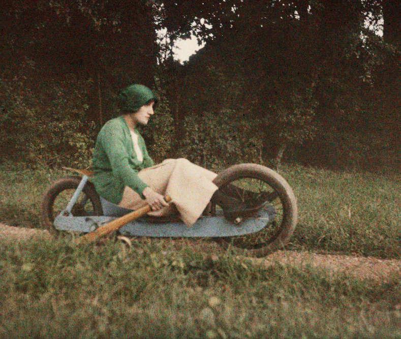 """Lartigue, âgé de 19 ans, écrit alors dans son journal: «Dessiné par moi et construit par mon ami Mauve, constructeur d'aéroplanes, voici le """"bob à deux roues"""". Il culbutait régulièrement dans les virages… C'est Simone Roussel, ma cousine, actionnant un des deux freins.» Simone est aussi le premier amour de Lartigue, mentionné en tant que tel dans son journal. Ici, typiquement à la manière de Lartigue, la couleur comme le mouvement sont autant de manières d'attraper l'insaisissable et la vie."""