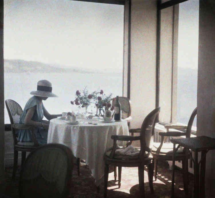 Cette photo est prise à l'hôtel du Cap d'Antibes, dans le salon de thé situé près de la petite piscine en pierre qui sera baptisée plus tard «Eden Roc». Ce lieu n'était pas aussi luxueux et snob qu'il l'est devenu ensuite. Cette image est une icône lartiguienne, si représentative d'une ambiance qui fait rêver – luxe et volupté, si faussement simple. Elle serait, parmi toutes celles de Lartigue, la photo préférée d'un grand nombre de ses admirateurs. Curieusement peu colorée, sans contraste fort, sans motif envahissant ni surcharge, elle brille par de subtils aplats de tons clairs, presque transparents. L'impression d'équilibre est admirable grâce à une distribution de vides et de pleins, de netteté (les objets sur la table) et de flou (la brume), de sec (les lignes) et de doux (les courbes).