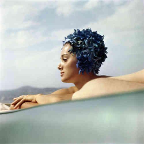 Sur la Côte d'Azur ou à Saint-Moritz, Jacques Lartigue croise à plusieurs reprises Sylvana et Wado Empain, avant le drame de 1978 qui les rendra célèbres. Il est sans doute fasciné par ce couple parfait à la fois riche et beau. Luxe, calme et volupté. A partir du profil de cette jolie femme, Lartigue invente une «créature» aux cheveux bleus et plastifiés, émergeant de la mer telle une sirène. Autour d'elle, ciel et mer composent une symphonie de tons subtils et de sensations océaniques. Le jeu (involontaire) des bras auquel vient s'ajouter un corps étranger forme un socle qui rehausse la splendeur de ce sphinx aquatique. Pour un photographe instinctif, les accidents de la vie peuvent avoir des effets heureux.
