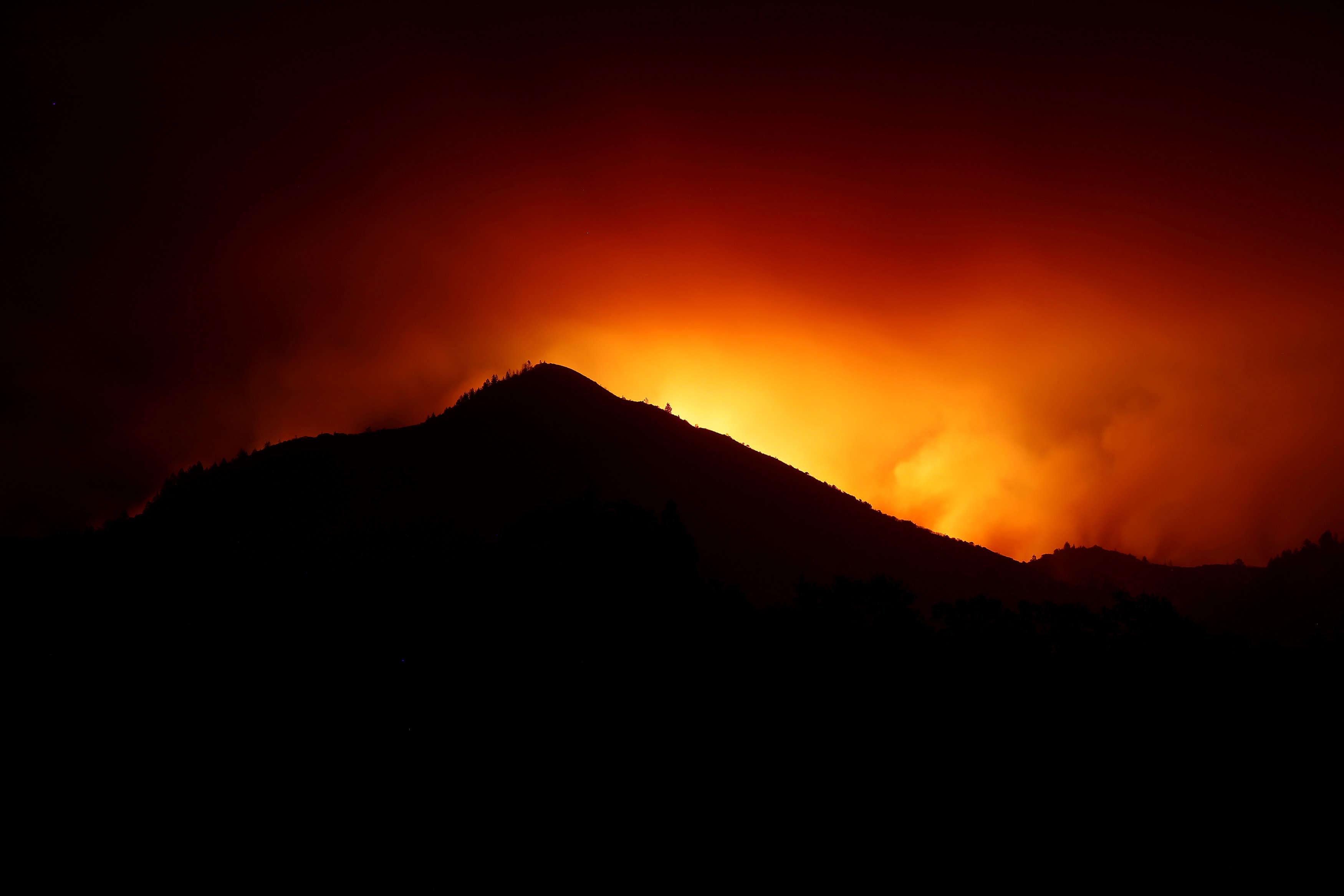 Lumière dégagée par les flammes au-dessus d'une colline à Kenwood, le 10 octobre.