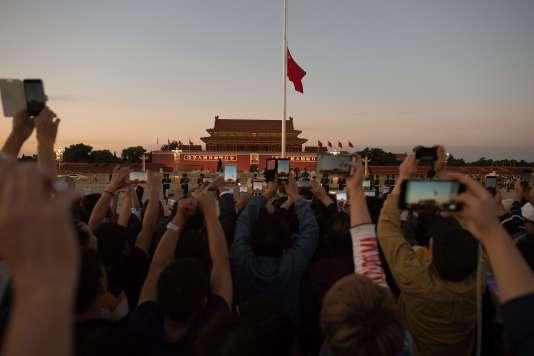 Des chinois photographient la mise en berne du drapeau sur la place Tiananmen à Pekin, le 28 septembre.