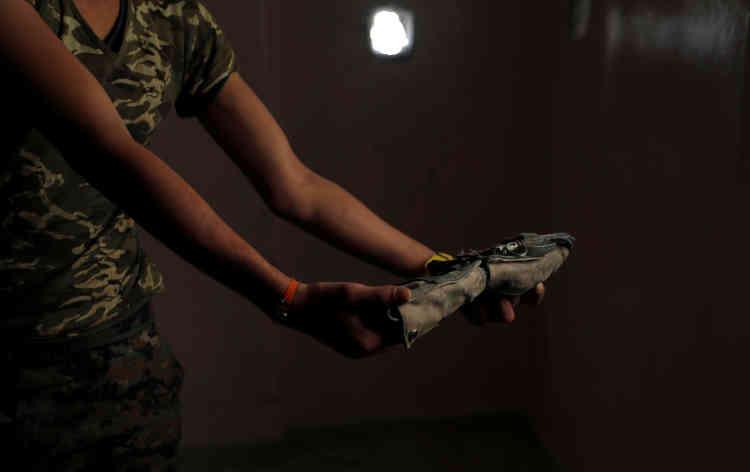 Un combattant des Forces démocratiques syriennes montre une ceinture de l'EI destinée à un attentat-suicide, le 4 octobre.