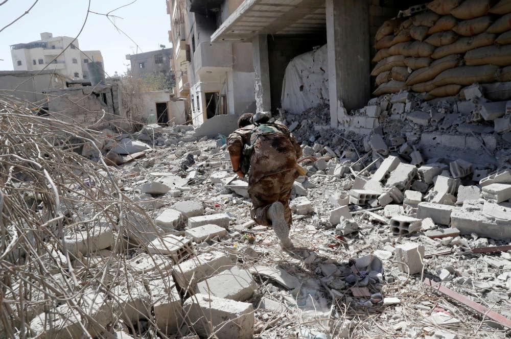 Un membre des Forces démocratiques syriennes tentent d'échapper aux tirs d'un sniper, près du stade de Rakka, le 4 octobre.