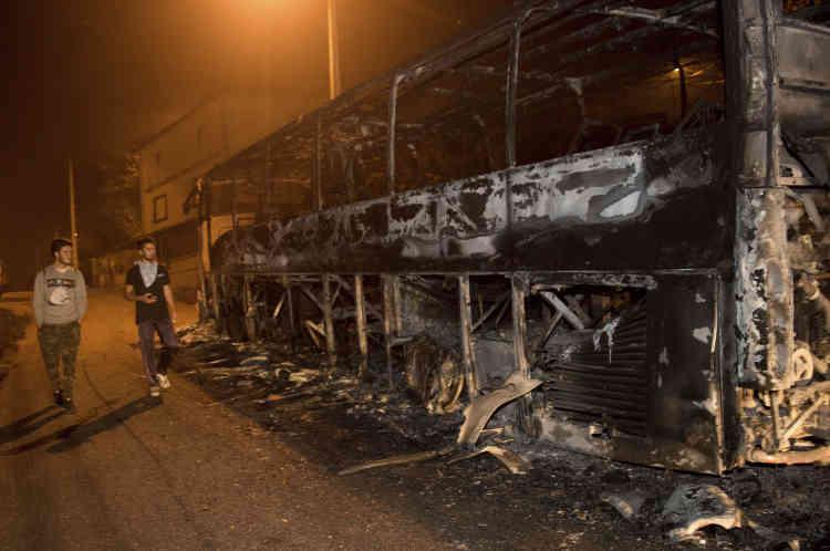 Des résidents passent devant un bus calciné alors qu'un incendie se propage à Chandebrito, Pontevedra, dans le nord-ouest de l'Espagne, en Galice, lundi16octobre.