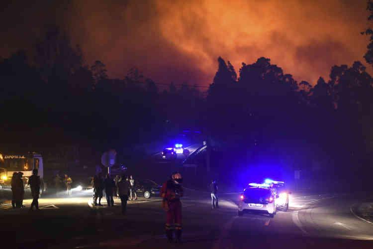 Des véhicules de police bloquent l'accès à la zone en flammes à As Neves, Pontevedra, dans le nord-ouest de l'Espagne, en Galice, lundi16octobre.