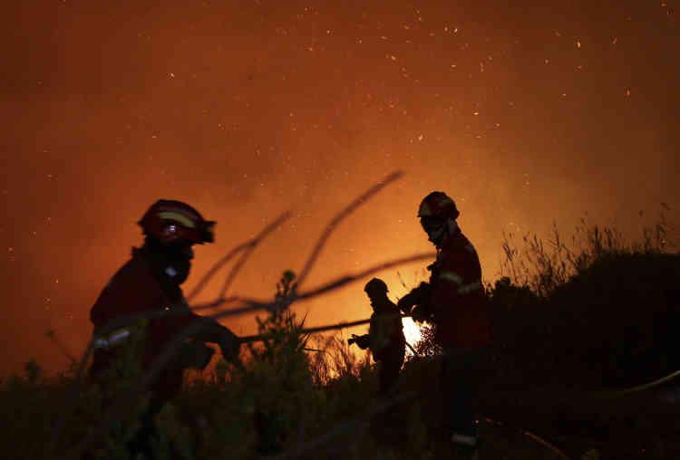 Des pompiers combattent le feu qui fait rage près des maisons à la périphérie d'Obidos, au Portugal, lundi 16 octobre.Vingt-sept personnes sont mortes dans le centre et le nord du Portugal dimanche et lundi matin, selon les services de la protection civile, cités par l'agence de presse portugaise Lusa.