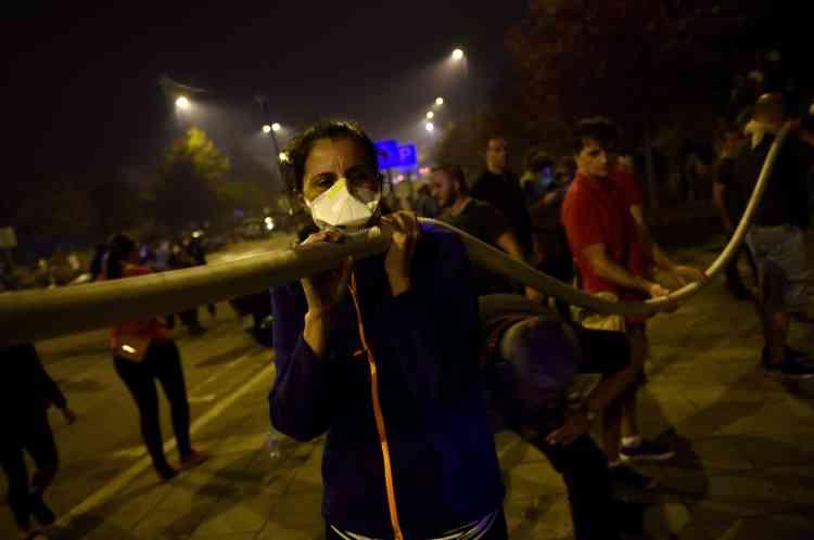 Des gens portent un tuyau pour aider à lutter contre un feu de forêt à Vigo, dans le nord-ouest de l'Espagne, le 15 octobre.