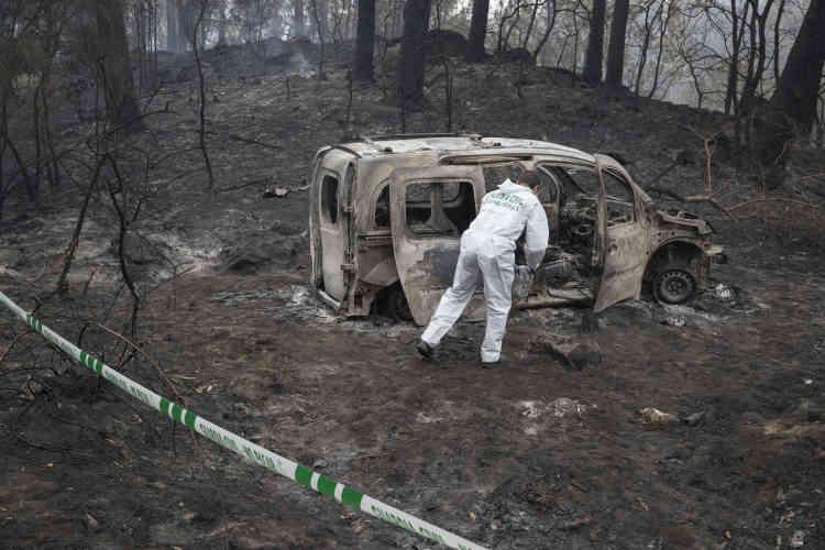 Un policier inspecte les restes de la voiture où deux femmes sont mortes à la suite d'un incendie de forêt à Pontevedra, dans le nord-ouest de l'Espagne, en Galice, lundi16octobre.