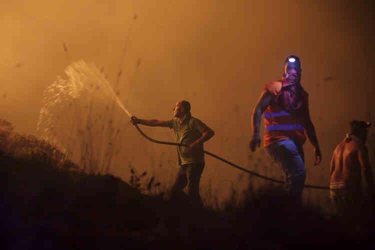 Des volontaires combattent le feu qui fait rage près des maisons dans la périphérie d'Obidos, au Portugal, dès les premières heures du lundi 16 octobre.Plus de 6000pompiers étaient mobilisés contre les incendies dimanche.