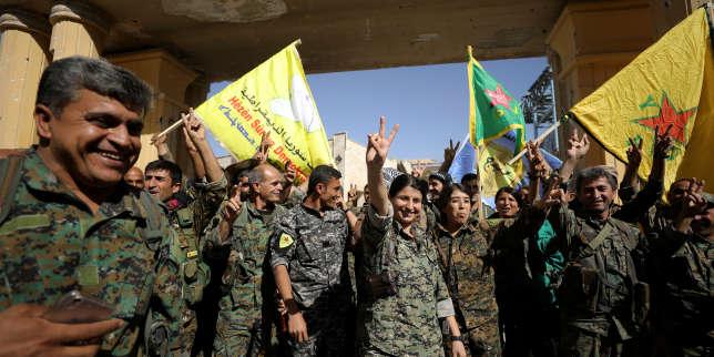 Des combattants des Forces démocratiques syriennes font le signe de la victoire à Raqqa, en Syrie, le 17 octobre.