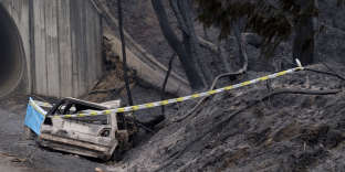 A burnt car in which an elderly couple was killed lies by the side of the road at the entrance of a small tunnel where it was caught by a wildfire in the village of Relvas near Santa Comba Dao, northern Portugal, Monday, Oct. 16 2017. Late season wildfires that broke out over the weekend in Portugal have killed at least 35 people, including a 1-month-old infant, authorities said Monday, making 2017 by far the deadliest year on record for forest blazes in the country. (AP Photo/Sergio Azenha)