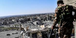 A member of the Syrian Democratic Forces (SDF), backed by US special forces, walks on a building near Raqa's stadium as they clear the last positions on the frontline on October 16, 2017 in the Islamic State (IS) group jihadists crumbling stronghold. US-backed fighters battled hundreds of Islamic State group jihadists holed up in the last pockets of Syria's Raqa, as the former extremist stronghold stood on the verge of capture. / AFP / BULENT KILIC