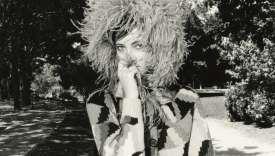 Gilet et jupe en laine, coiffe en plume de marabout, Prada. Sac en cuir, Balenciaga.