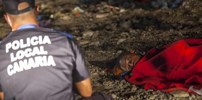 Un migrant regarde un policier espagnol sur une plage de Grande Canarie, après l'arrivée d'un bateau transportant une soixantaine depersonnes, le 1er septembre 2015.