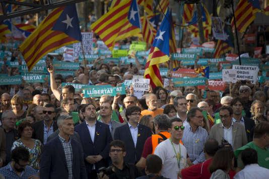 Le président catalan Carles Puigdemont (au centre avec des lunettes) lors d'une manifestation à Barcelone le 21 octobre.