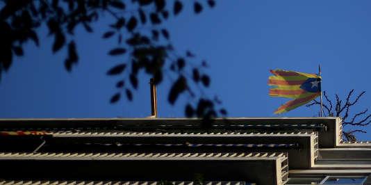 Un drapeau catalan endommagé flotte à un balcon de Barcelone, le 20 octobre.