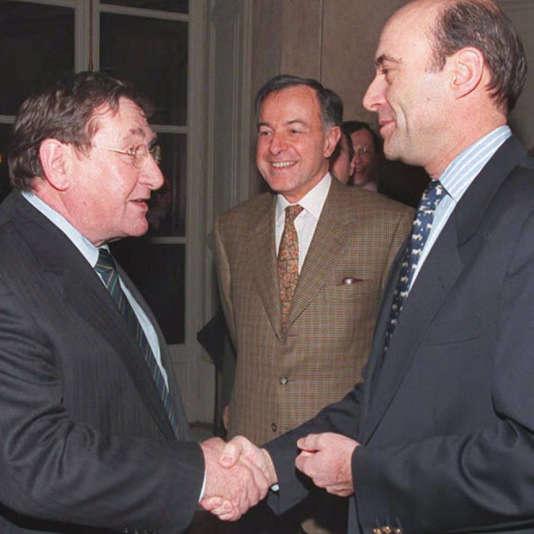 Louis Viannet (à gauche) serre la main du premier ministre Alain Juppé (à droite) sous les yeux d'Alain Lamassoure, alors porte-parole du gouvernement, le 21 décembre 1995.