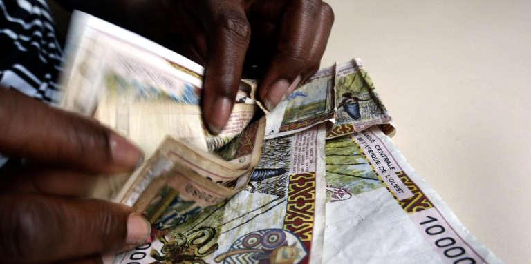 Une caissière compte des billets de 10000francs CFA, à Abidjan, en avril 2002.