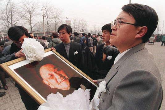 Le public attend le passage du convoi funéraire de Deng Xiaoping, sur la route du cimetière révolutionnaire de Babaoshan, à Pékin, le 24 février 1997.