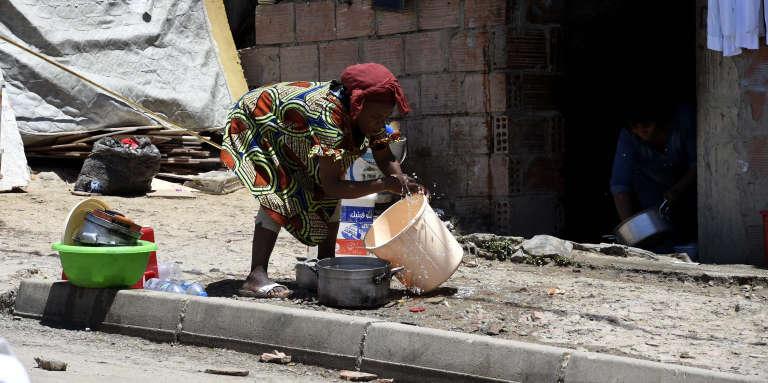 Une femme d'origine subsaharienne fait la vaisselle devant un bâtiment en construction occupé par des migrants, à Alger, en mai 2016.