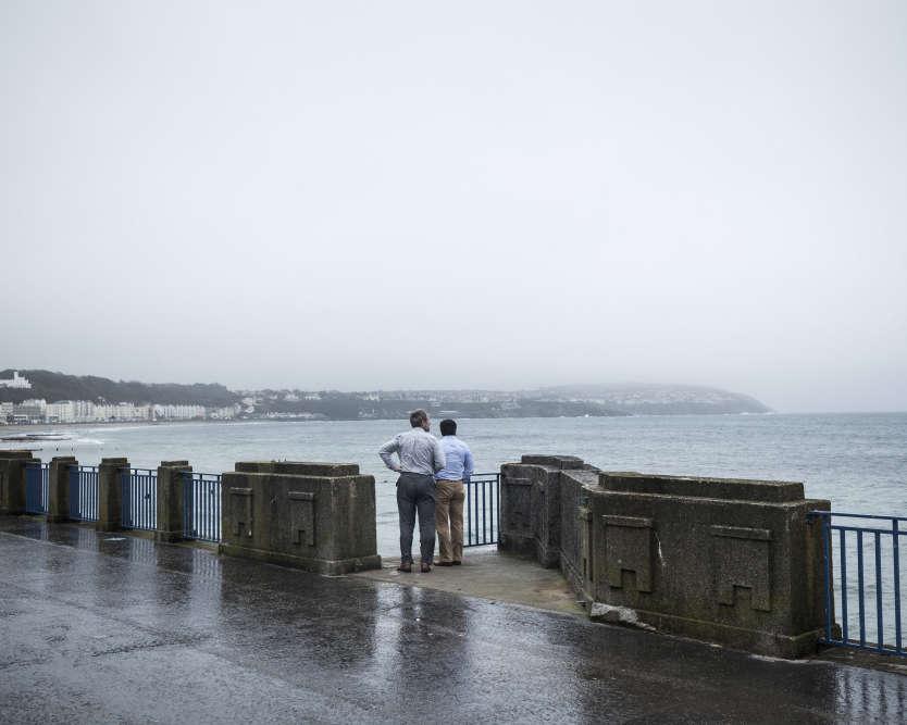 A Douglas, la capitale, deux employés regardent la mer d'Irlande. L'île de Man abrite 30000sociétés pour 88000habitants, de nombreux cabinets proposant des services offshore. Par exemple, de temps à autre, un gigantesque yacht fait escale dans la baie pour s'immatriculer dans cette île réputée pour ses avantages fiscaux.