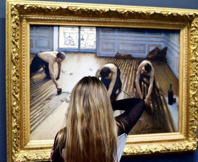 Une jeune fille regarde« Les Raboteurs de parquet», de Gustave Caillebotte, au Musée d'Orsay (Paris).