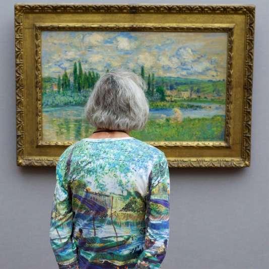 Une femme avec un T-shirt imprimé d'un tableau impressionniste admire une œuvre de Claude Monet, à Berlin.