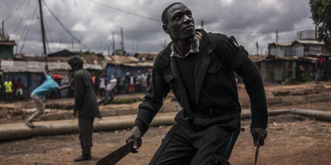 Un homme brandit une machette et un couteau lors d'affrontements avec les forces de l'ordre dans le quartier de Kibera, à Nairobi, lors de l'élection présidentielle kényane, le 26octobre 2017.