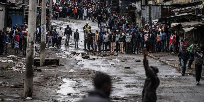 Des habitants du bidonville de Mathare, à Nairobi, observent un groupe d'opposants essayant d'empêcher l'accès au bureau de vote lors de l'élection présidentielle kényane, le 26octobre 2017.