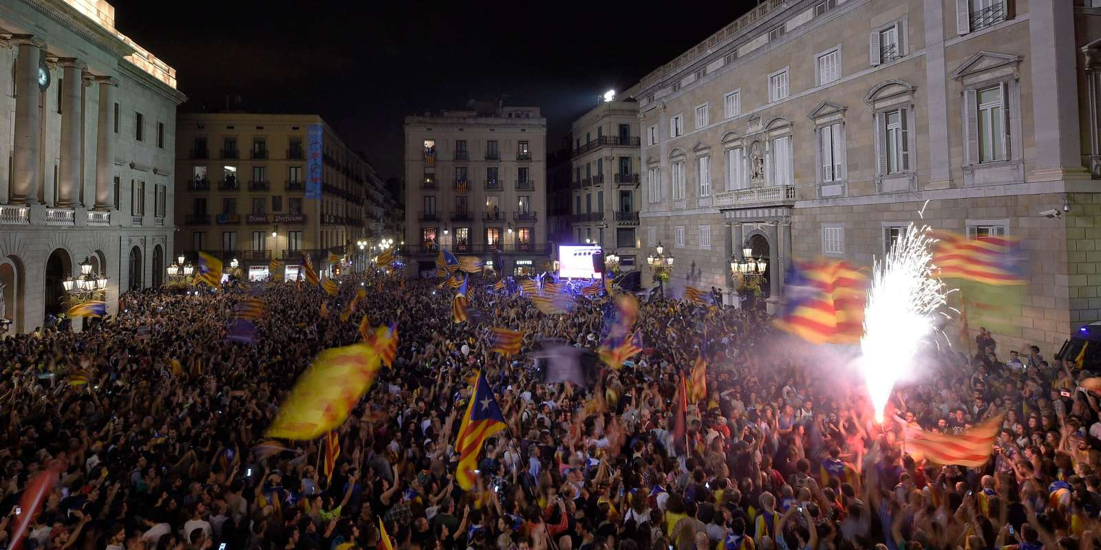 People gather in front of the 'Generalitat' palace (Catalan government headquarters) at the Sant Jaume square to celebrate the proclamation of a Catalan republic in Barcelona on October 27, 2017. Catalonia's parliament voted to declare independence from Spain and proclaim a republic, just as Madrid is poised to impose direct rule on the region to stop it in its tracks. A motion declaring independence was approved with 70 votes in favour, 10 against and two abstentions, with Catalan opposition MPs walking out of the 135-seat chamber before the vote in protest at a declaration unlikely to be given official recognition. / AFP / LLUIS GENE