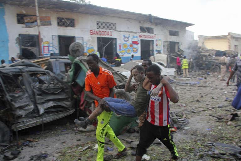 Des habitants portent un homme blessé après l'explosion d'une voiture piégée à Mogadiscio le 28 octobre