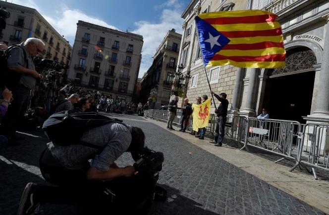Un homme brandissant un drapeau indépendantiste devant des dizaines de caméras, sur la place St Jaume, devant les portes de la Generalitat à Barcelone, lundi 30 octobre.