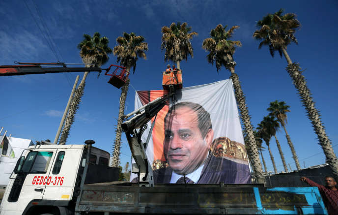 Des Palestiniens installent une affiche du président égyptien, Abdel Fattah Al-Sissi, au point de passage de Rafah, au sud de la bande de Gaza,le 1er novembre.