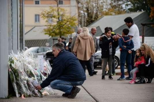 Un homme dépose des fleurs devant le bar tenu par les parents d'Alexia Daval, dont le corps a été retrouvé lundi.