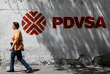 A woman walks past a mural with the corporate logo of the state oil company PDVSA in Caracas, Venezuela November 3, 2017. REUTERS/Marco Bello