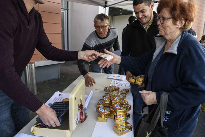 Une cliente achète du beurre vendu au« juste prix» par des agriculteurs devant un supermarché à Civrieux-d'Azergues, près de Lyon.