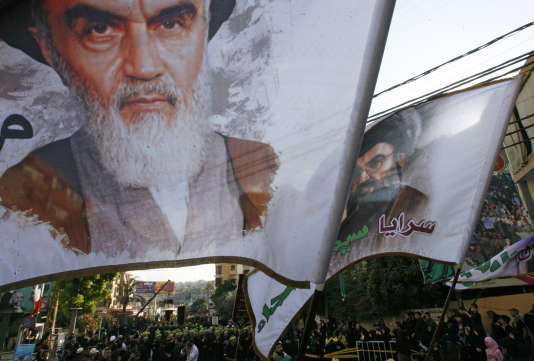 Des partisans du Hezbollah avec des drapeaux montrant l'ayatollah Khomeini et le dirigeant du Hezbollah, Hasan Nasrallah.