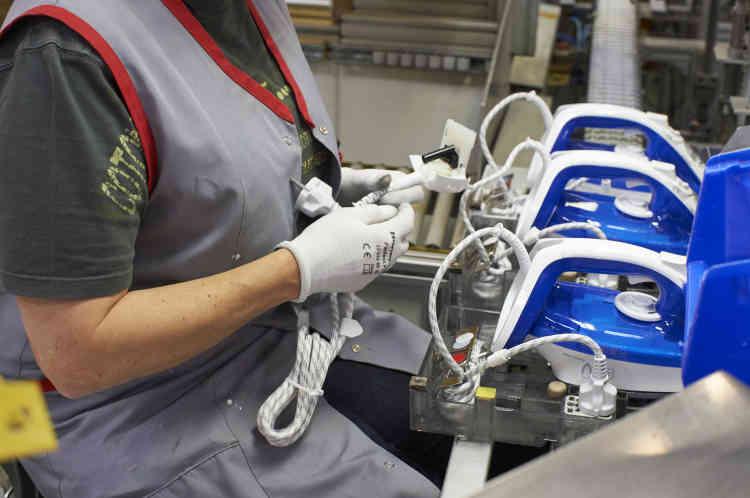Sur la chaîne, l'essentiel des tâches est effectué par des machines. Des ouvrières assurent encore quelques finitions. Elles insèrent à la main la molette du thermostat et le cordon.