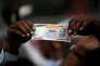 «Dans un pays où 90 % de la population travaille pour le secteur informel, la fin des vieux billets a ébranlé les micro-entreprises et pris à la gorge les plus pauvres, les paysans modestes et tous les exclus du système bancaire. ». (Photo : Un opposant à la démonétisation, impulsée par le premier ministre Narendra Modi, arbore un faux billet de 1000 roupies lors d'une manifestation à l'occasion du premier anniversaire de la mesure. A Ahmedabad (Inde), le 8 novembre).