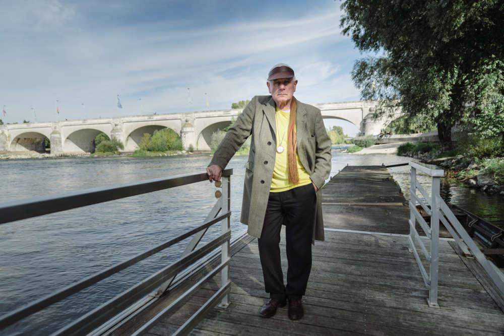 """«Pour la réactivation de cette installation historique, Klaus Rinke et l'équipe du CCCOD ont mené une grande campagne de puisage d'eau de 12 rivières et fleuves européens, depuis le Danube que surplombe Klaus Rinke toute l'année en Autriche, jusqu'à la Loire, située à deux pas du centre d'art tourangeau. Ici, l'artiste pose après avoir récolté l'eau de la Loire qu'il intègrera dans la machinerie de l'""""Instrumentarium"""".»"""