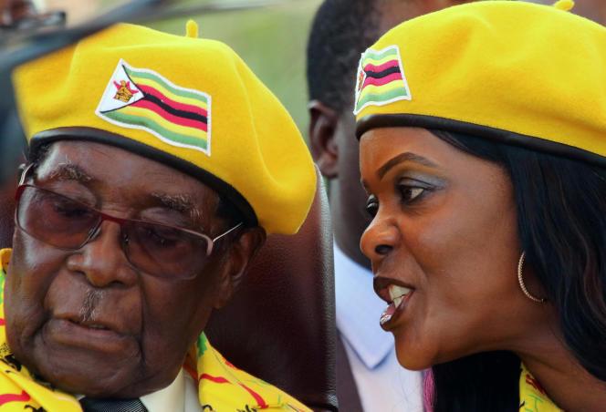 President Robert Mugabe listens to his wife Grace Mugabe at a rally of his ruling ZANU-PF party in Harare, Zimbabwe, November 8, 2017.REUTERS/Philimon Bulawayo