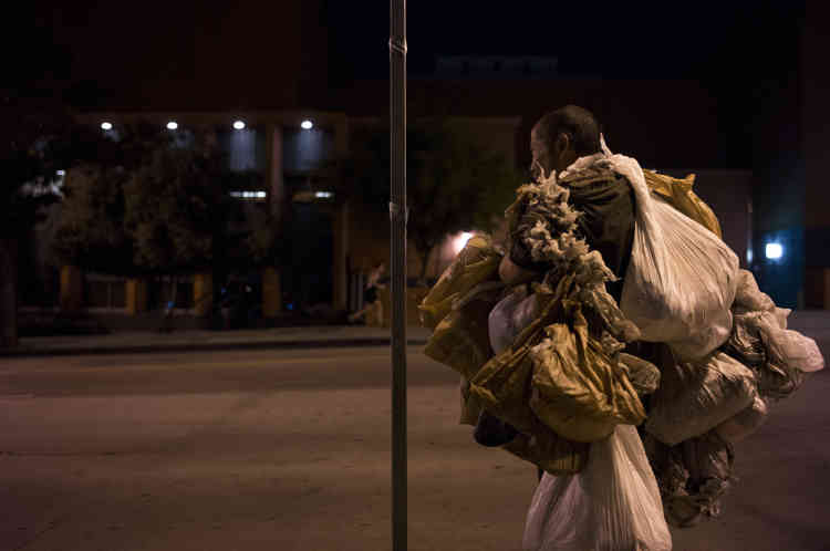 Transportant des sacs en plastique contenant ses affaires, un sans-abri, qui a refusé de donner son nom, fait une pause sur un trottoir jeudi 21 septembre, à Los Angeles. Selon le compte annuel publié enmai par Los Angeles Homeless Services Authority, le nombre de sans-abri dans le comté de Los Angeles est de 57794personnes, soit un bond de23% par rapport à l'an dernier.