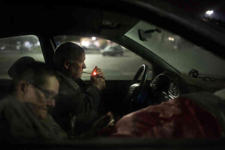 Kerry Schmid, 59 ans, et Teri Angus-Lydell, 64 ans, au premier plan, sont assis dans une petite voiture où ils dorment la nuit dans le parking d'un magasin Walmart , le29septembre, à Huntington Beach, en Californie. Schmid vit dans sa voiture depuis 2000 et Angus-Lydell l'a rejoint il y a environ un mois en quête de sécurité. Plus d'une douzaine de sans-abri dorment dans le parking, y compris le frère de Schmid. «Je suis reconnaissant, c'est comme un palais pour moi», a déclaré Schmid.