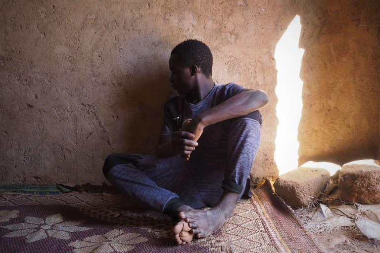 Souleyman, jeune Guinéen de 14 ans, attend de réunir les 800 000CFA (1200e) nécessaires pour partir en Italie via la Libye. Il est arrivé de la Guinée il y a 3 semaines. Dans un ghetto du quartier Tadresse. Agadez, le 6 novembre 2017.